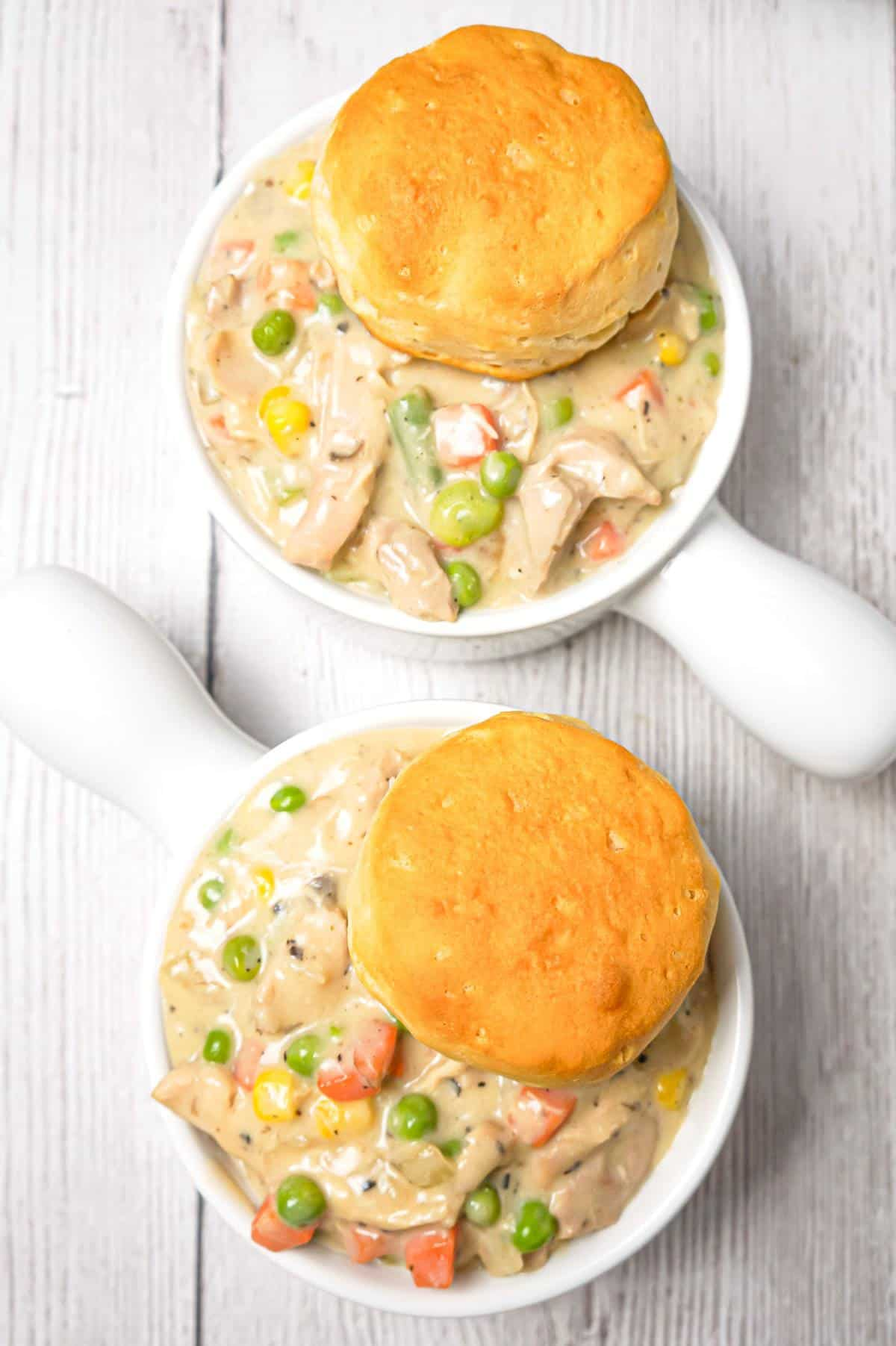 Crock Pot Chicken Pot Pie is an easy slow cooker dinner recipe made with boneless, skinless chicken thighs, cream of mushroom soup, cream of chicken soup and mixed veggies and topped with Pillsbury biscuits.