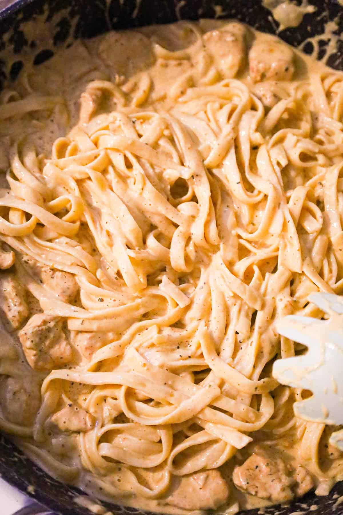 cajun chicken fettuccine alfredo being stirred in a saute pan