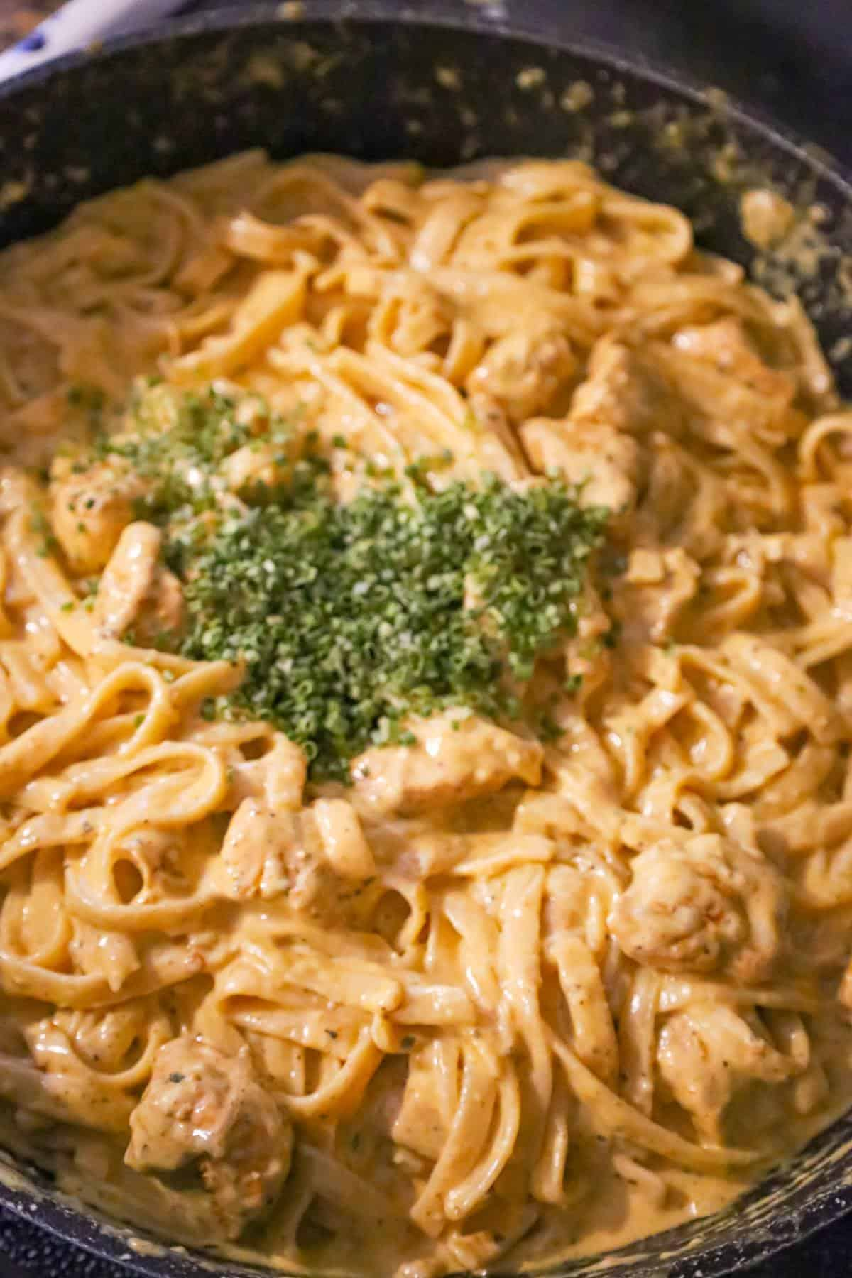 chopped chives on top of cajun chicken alfredo in a saute pan