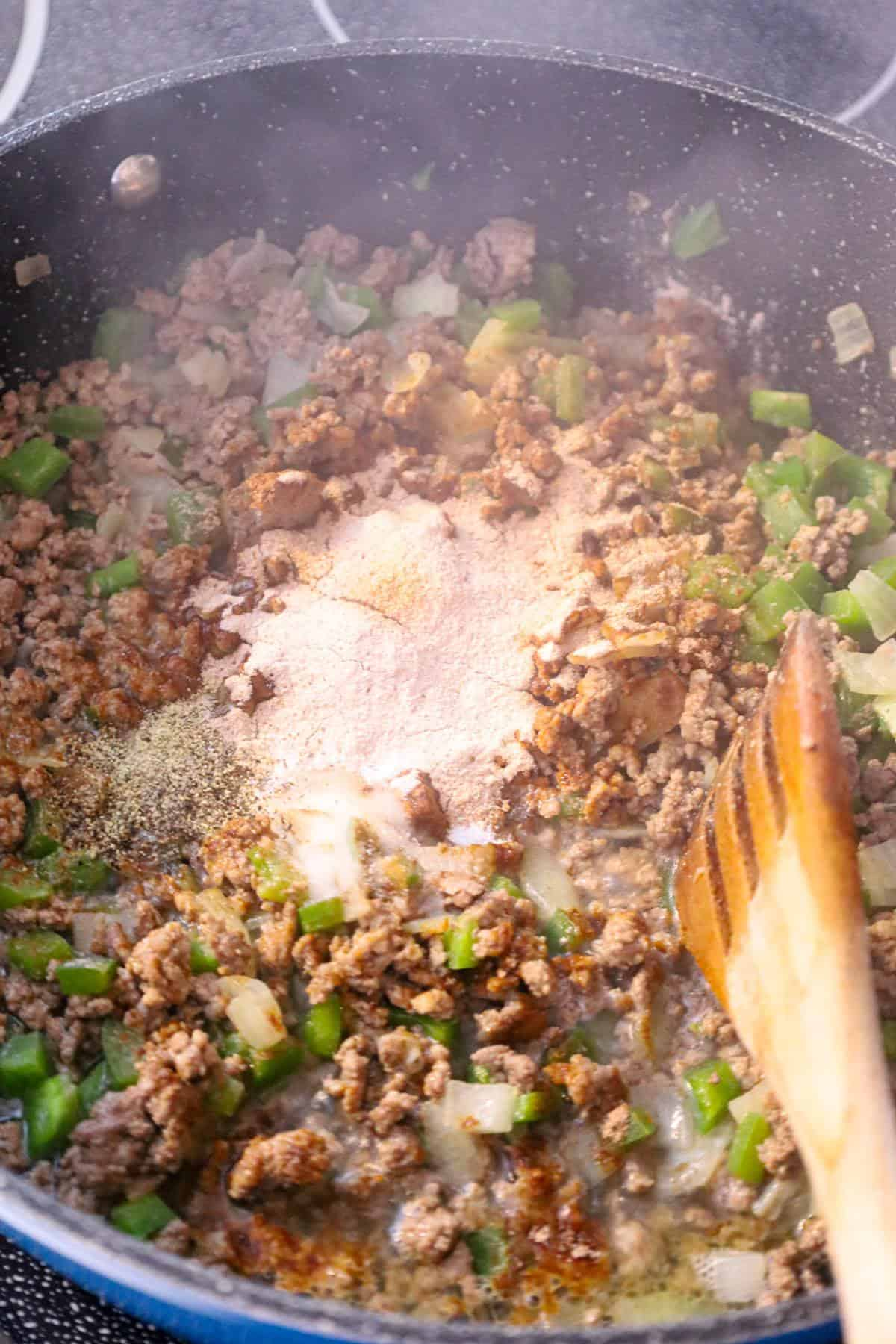 brown gravy mix on top of cooked ground and diced green peppers and diced onions
