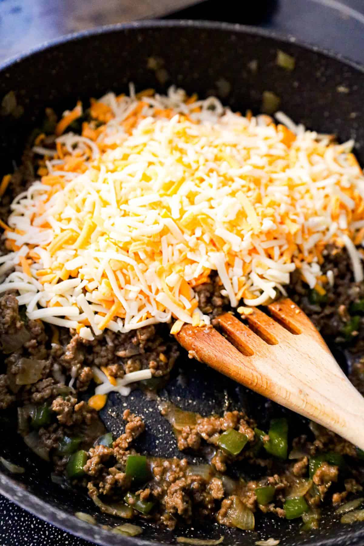 shredded mozzarella and cheddar cheese on top of ground beef mixture in a saute pan