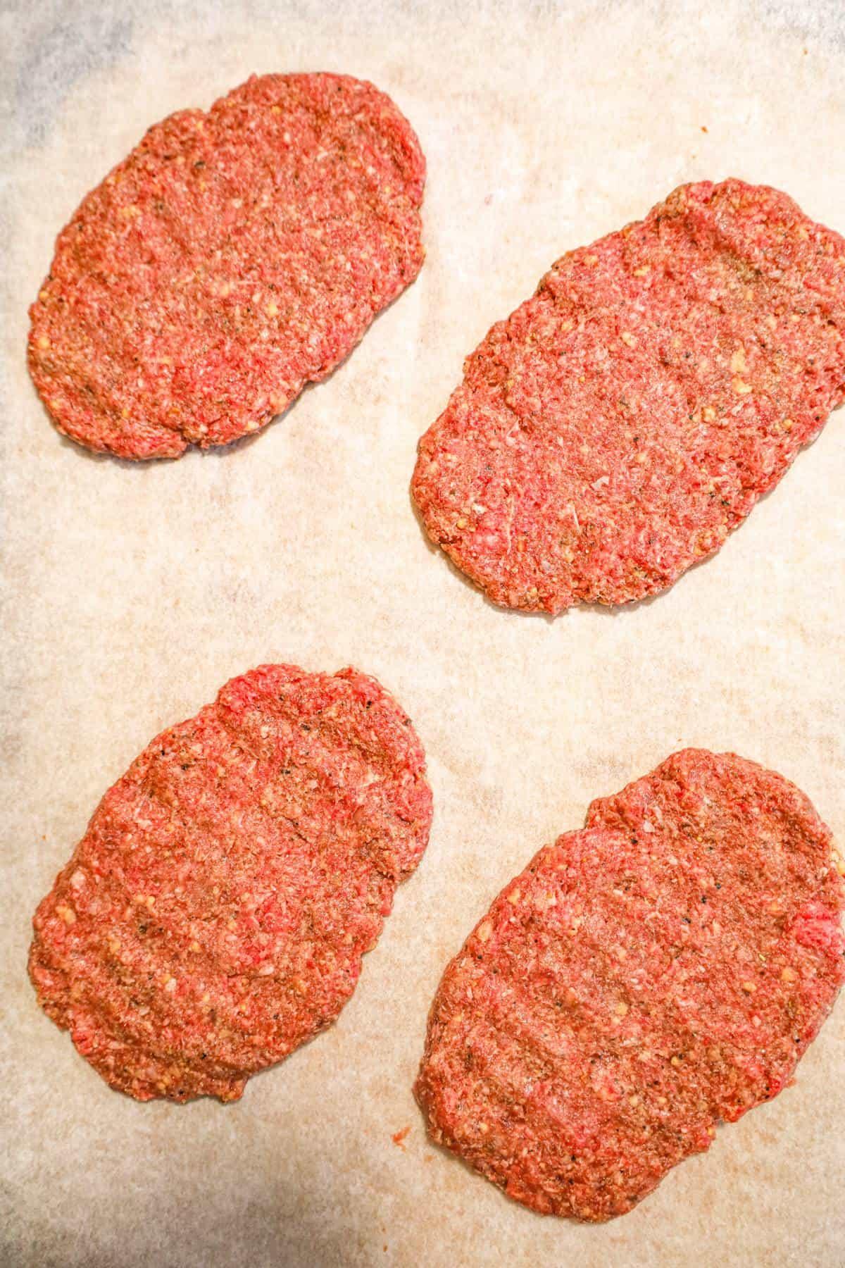raw hamburger patties on parchment paper
