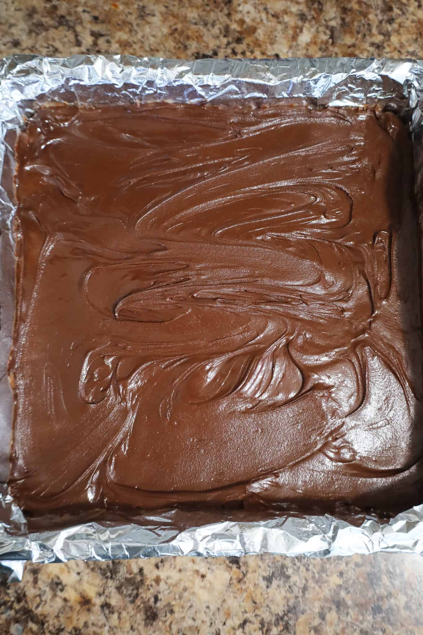 melted chocolate spread on top of peanut butter bars in a baking pan