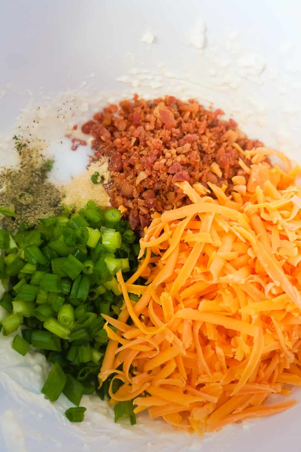 shredded cheddar cheese, real bacon bits and chopped green onions in a mixing bowl