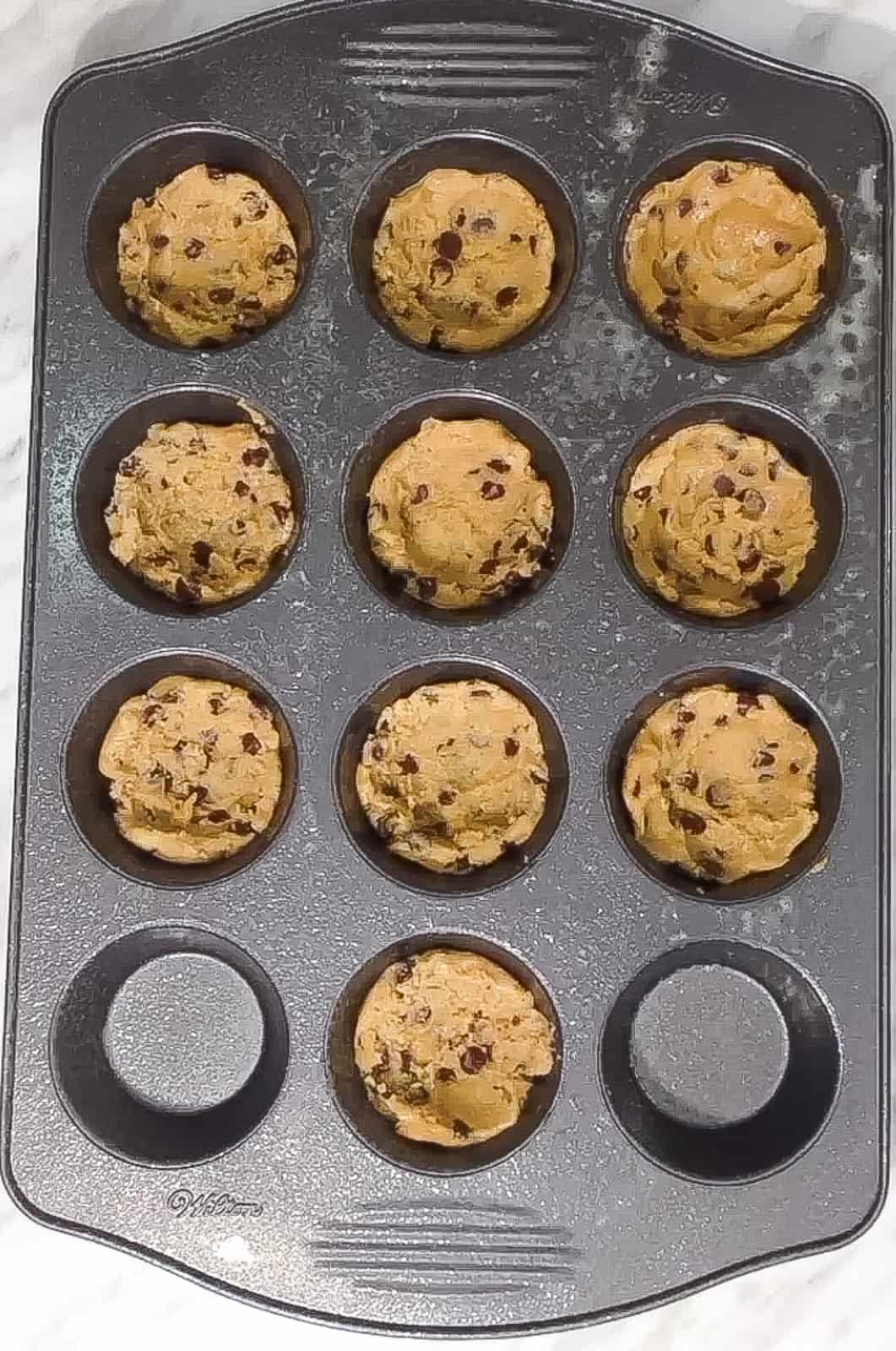 chocolate chip cookie dough in muffin tins