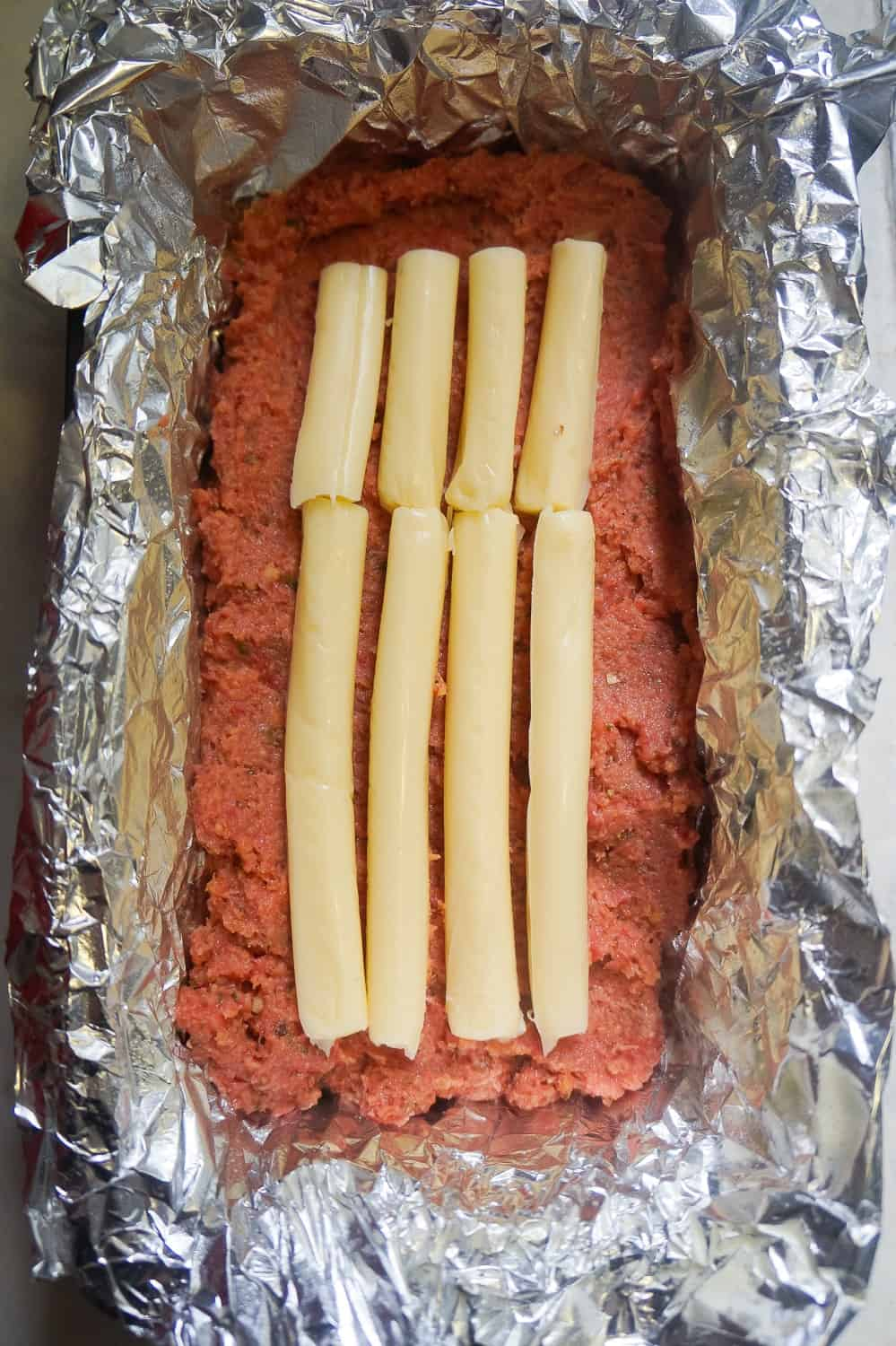 string cheese in the center of uncooked ground chicken meatloaf