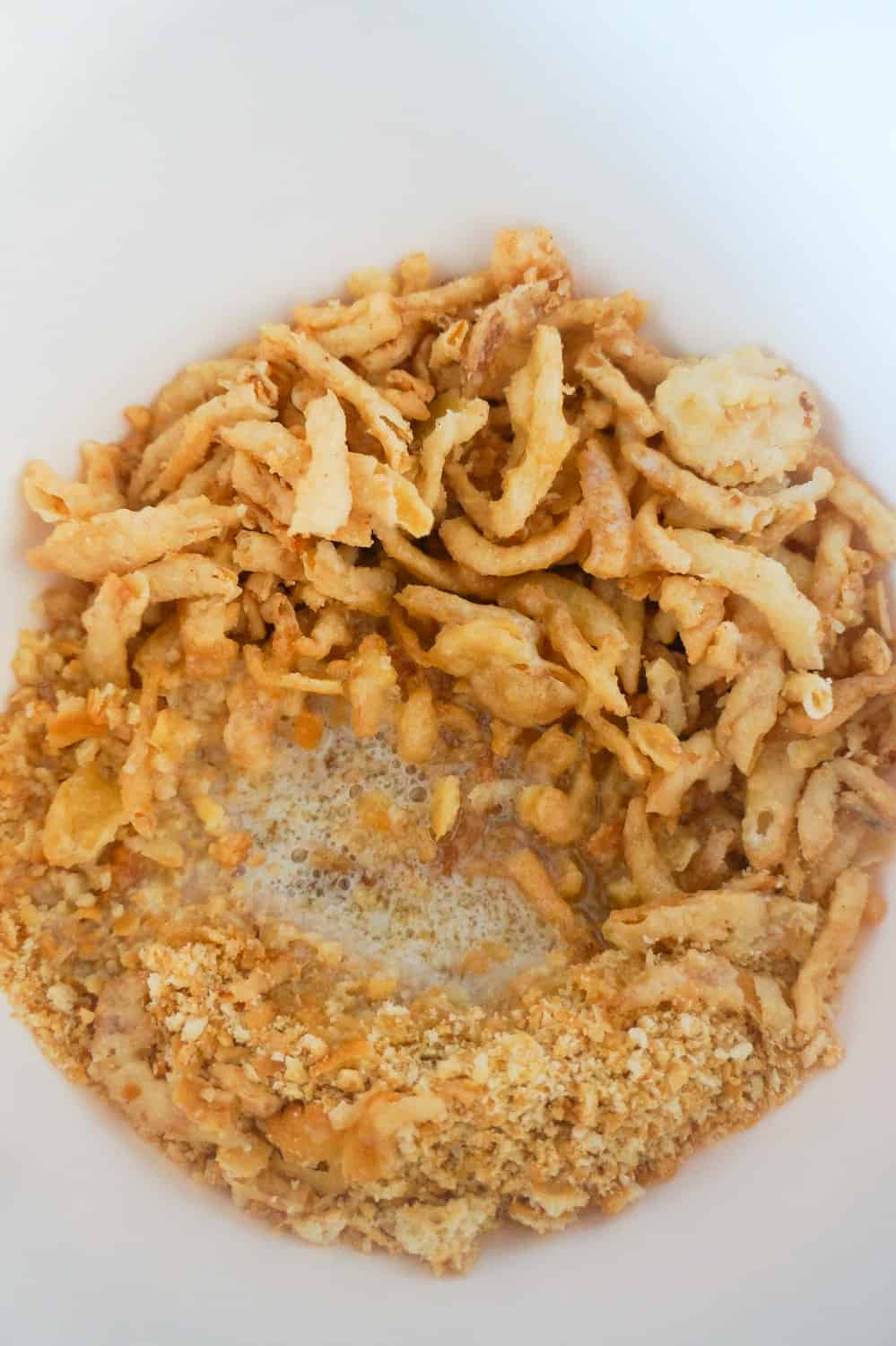 crushed Ritz crackers, fried onions and melted butter in a mixing bowl