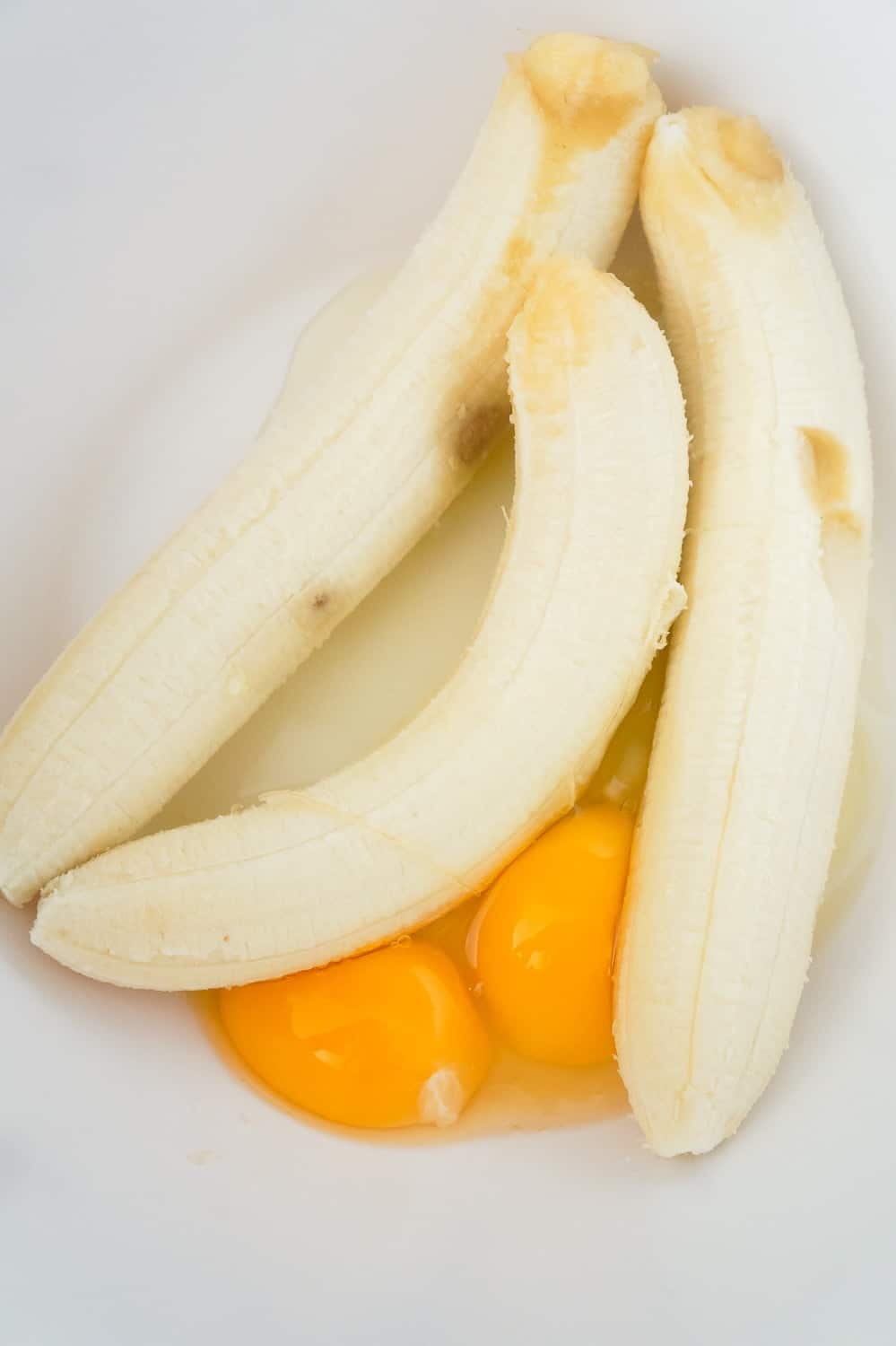 ripe bananas and eggs in a large mixing bowl
