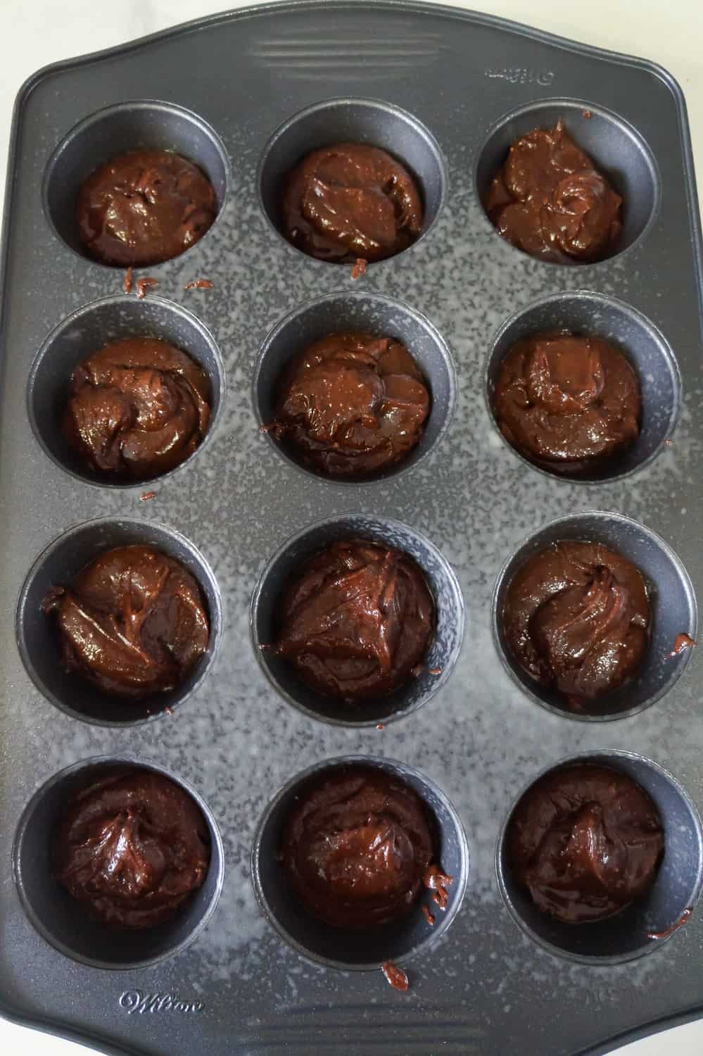 brownie batter in muffin tins