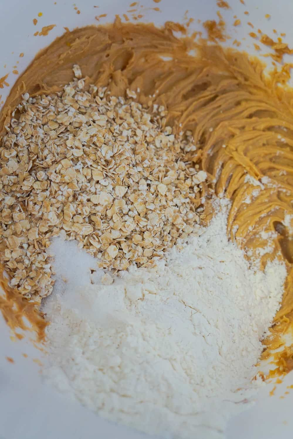 flour and oats added to peanut butter mixture in mixing bowl