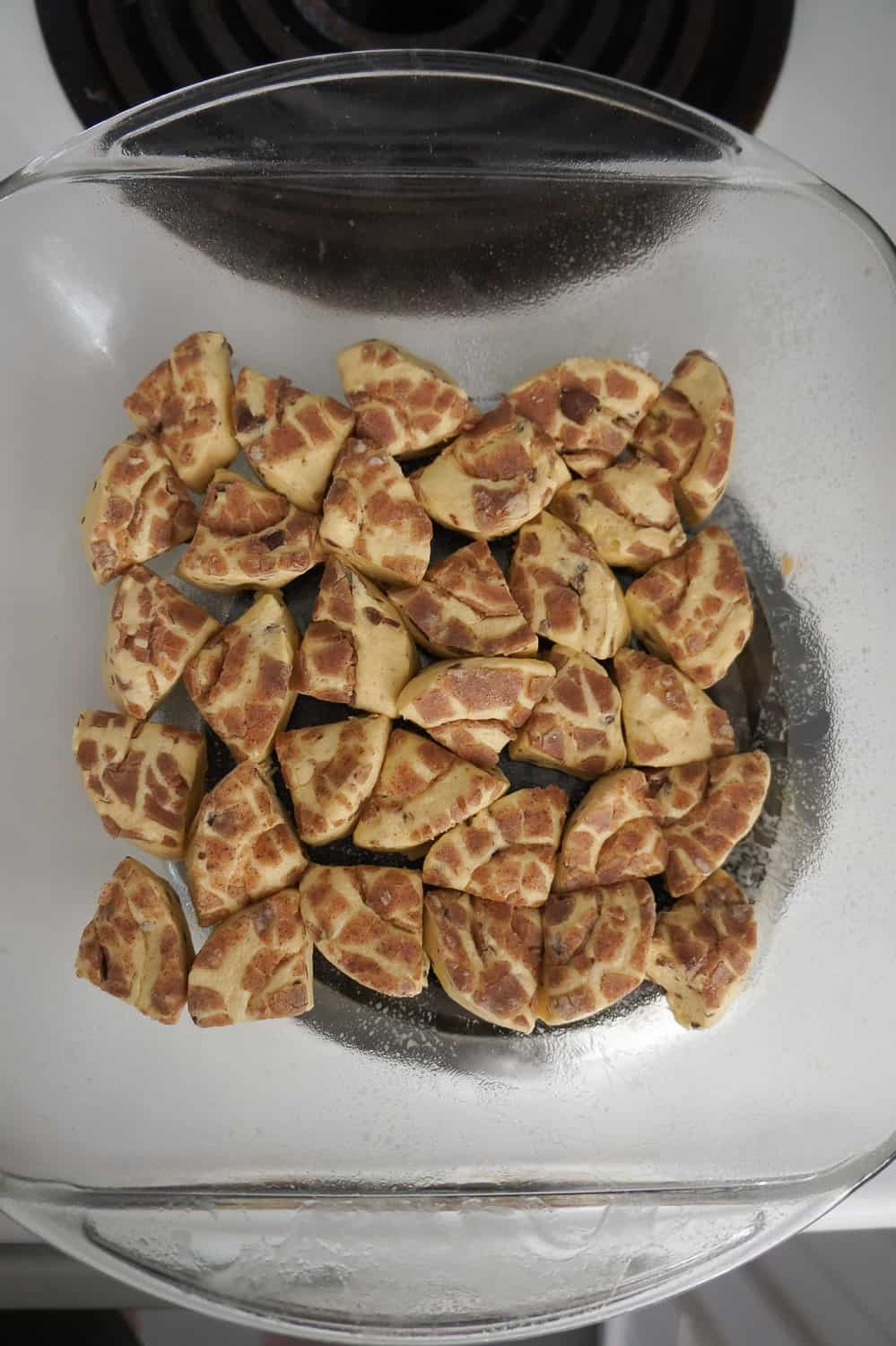 pieces of pillsbury cinnamon roll dough in the bottom of a baking dish