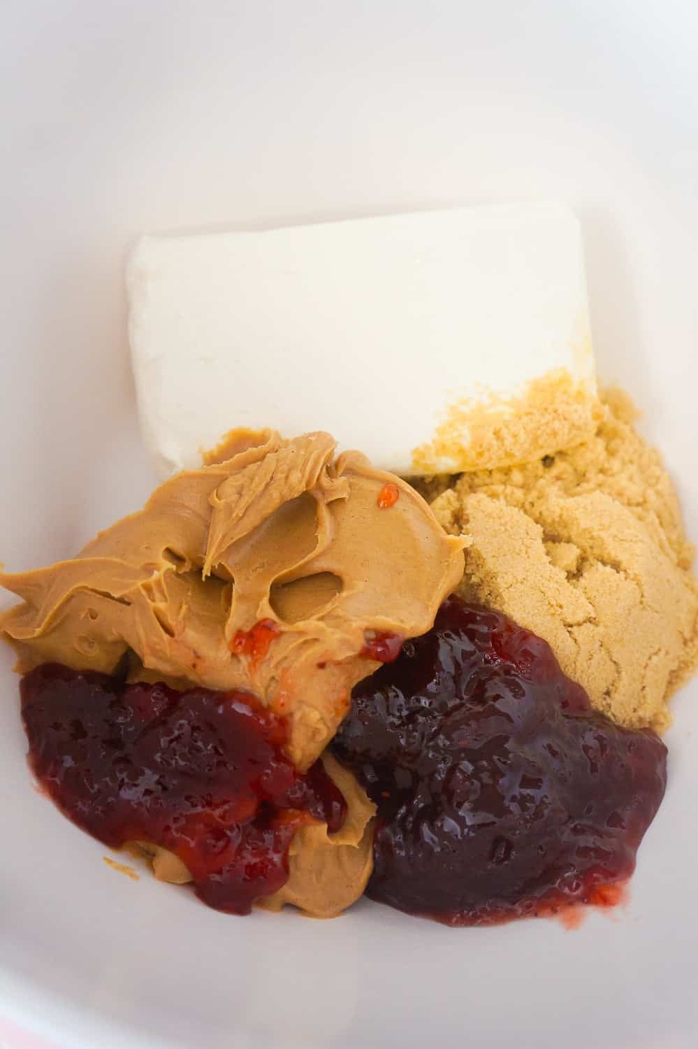cream cheese, peanut butter, brown sugar and strawberry jam in a mixing bowl