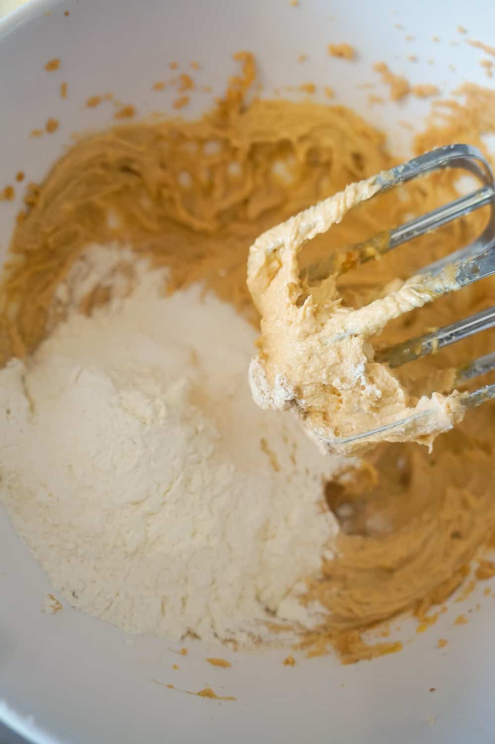 flour being added to peanut butter cookie dough in mixing bowl